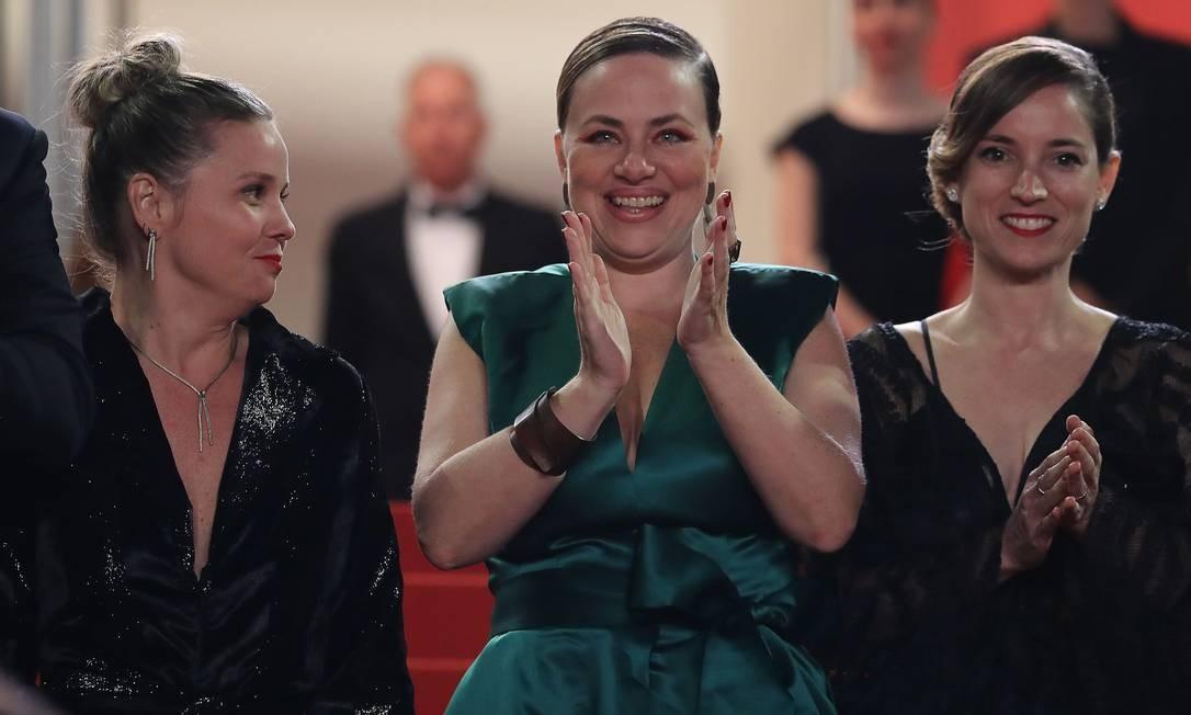 A atriz Karine Teles aplaude, com a produtora francesa Emile Lesclaux ao lado direito Foto: VALERY HACHE / AFP