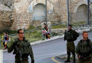 Crianças palestinas vão para escola enquanto militares israelenses patrulham a cidade de Hebron, na Cisjordânia ocupada: colonização da região é política do governo israelense desde que ela foi tomada em 1967 Foto: MUSSA ISSA QAWASMA/REUTERS