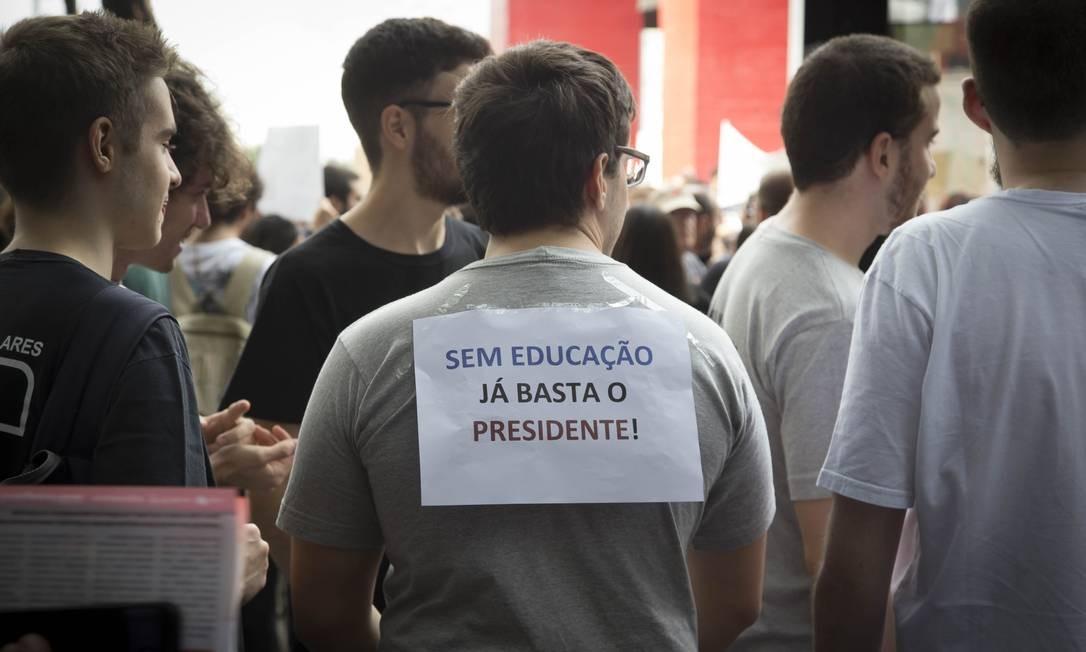 Jovem carrega cartaz colado nas costas com crítica ao presidente Bolsonaro Foto: Edilson Dantas / Agência O Globo