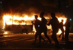 Manifestantes passam em frente a ônibus incendiado Foto: Domingos Peixoto / Agência O Globo