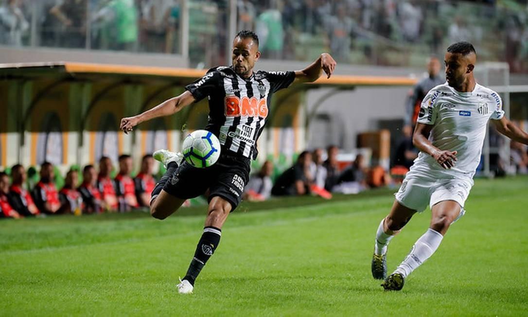 Jorge, do Santos, observa o chute de Geuvânio, do Atlético-MG Foto: BRUNO S.C.JUNIOR/Atlético-MG