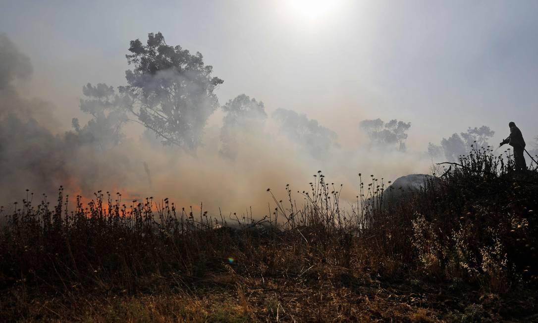 Um israelense apaga chamas em um campo ao lado do kibutz Beeri. O incêndio foi supostamente causado por material inflamável preso a pipas e levado através da fronteira para Israel a partir da Faixa de Gaza Foto: MENAHEM KAHANA / AFP