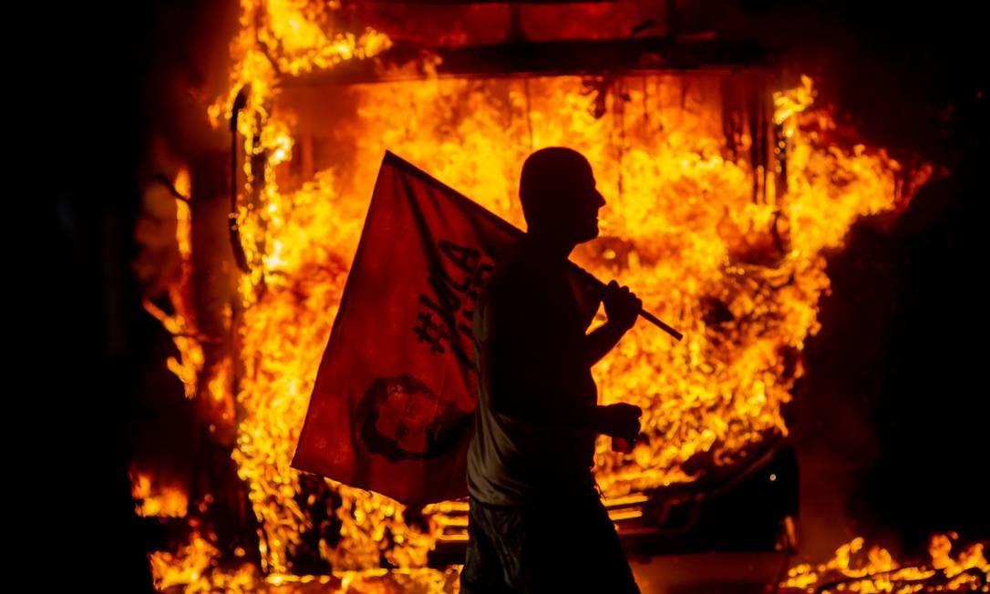Um homem segura uma bandeira representando o ex-presidente brasileiro Luiz Inácio Lula da Silva diante de um ônibus em chamas durante um protesto organizado pela União Nacional dos Estudantes (UNE) no Rio de Janeiro. Alunos e professores de centenas de universidades e faculdades em todo o Brasil manifestaram-se em defesa da educação após uma série de cortes orçamentários anunciados pelo governo do presidente Jair Bolsonaro Foto: MAURO PIMENTEL / AFP