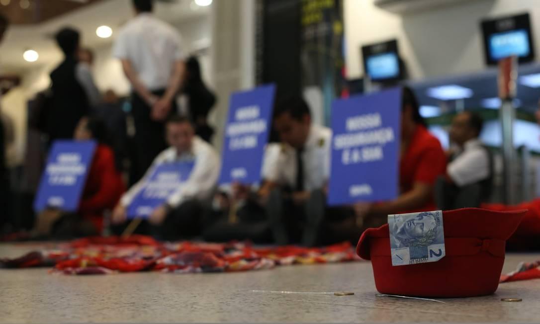 Sentados no saguão do aeroporto Santos Dumont, no Rio, os funcionários da aérea protestavam contra o atraso dos salários Foto: Pedro Teixeira / Agência O Globo