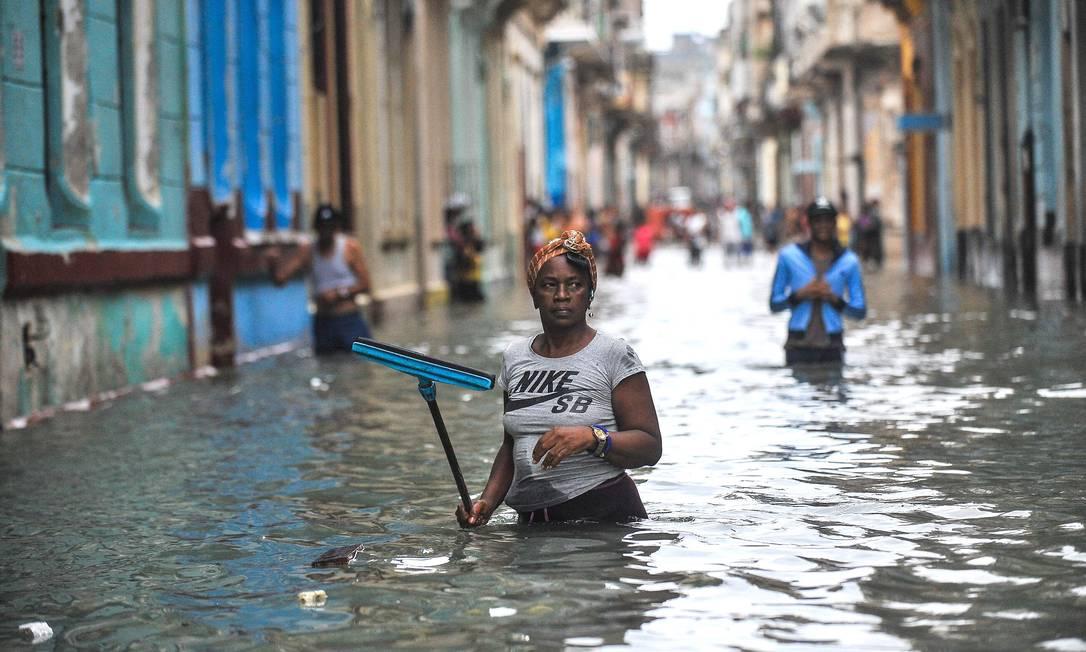 Cubanos andam por rua inundada em Havana após furacão: ritmo das mudanças climáticas preocupam o mundo Foto: YAMIL LAGE / AFP/10-9-2017