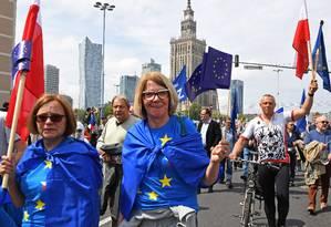 Poloneses carregando bandeiras da União Europeia participam de marcha neste sábado celebrando os 15 anos da adesão do país ao bloco, às vésperas de nova eleição para o Parlamento Europeu Foto: JANEK SKARZYNSKI / AFP