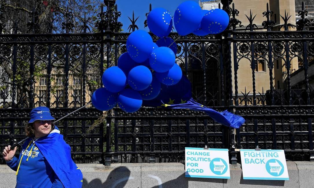 Manifestante contrário à saída do Reino Unido da UE passa por cartazes do Partido do Brexit, de Farage, diante do Parlamento, em Londres: trabalhistas e conservadores devem ficar em 2º e 3º lugares Foto: Toby Melville/REUTERS/16-5-2019