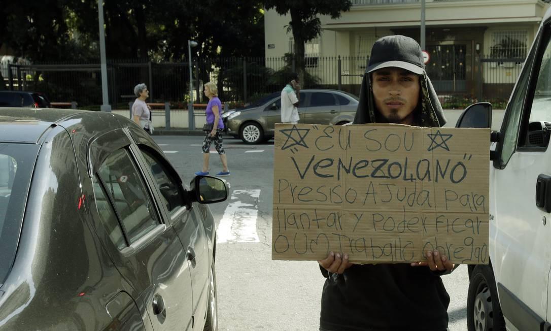 O venezuelano Felipe Cruz Gallo pede ajuda para chegar ao Uruguai nas esquinas da rua Ipiranga e Laranjeiras, 25 de maio de 2019. Foto: Antonio Scorza / Agência O Globo