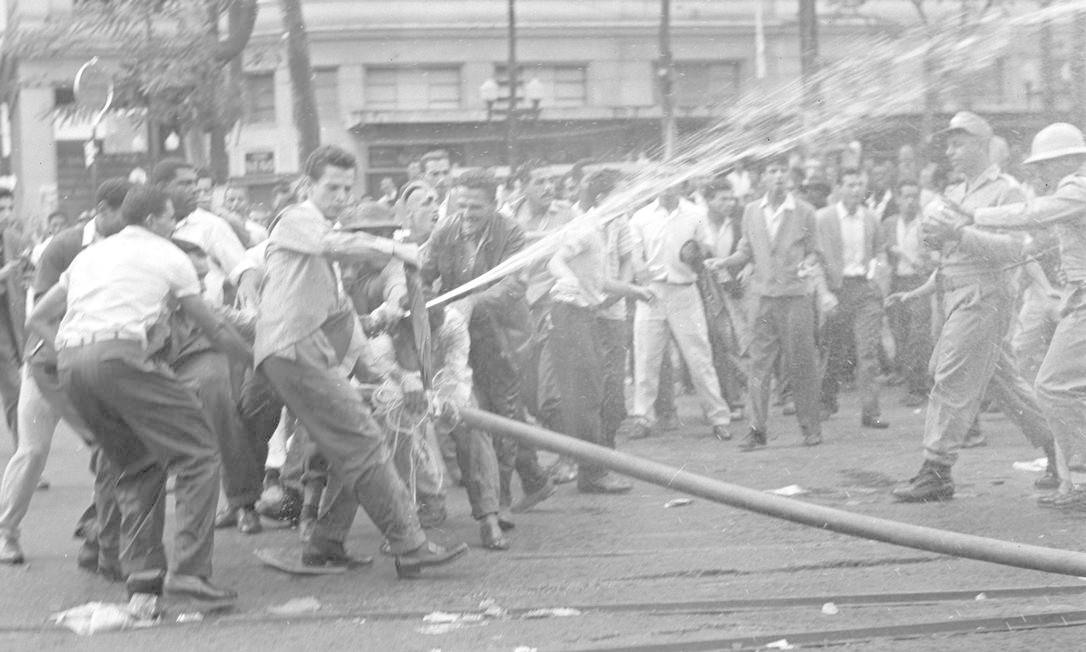 Manifestantes tentam impedir os bombeiros, que foram agredidos a pedradas, de debalarem o fogo Foto: Arquivo/O Globo