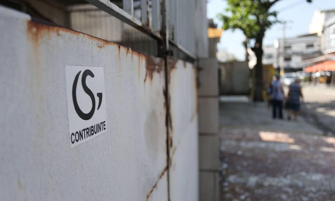 """Milícia marca com adesivos casas de moradores """"contribuintes"""" em Irajá. Na foto, adesivos em uma casa na Rua São Leonardo Foto: Pedro Teixeira / Agência O Globo"""