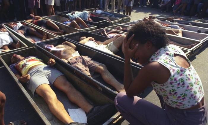 Parente chora diante dos cadáveres das 21 pessoas mortas na chacina de Vigário Geral Foto: Custódio Coimbra/30-8-1993 / Agência O Globo