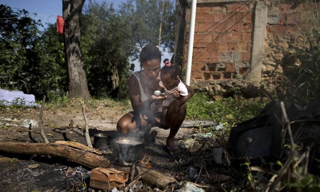 Patrícia Aguiar, com a filha Ana Beatriz no colo, prepara o almoço em fogão improvisado sobre madeiras no quintal de sua casa Foto: Márcia Foletto / Agência O Globo