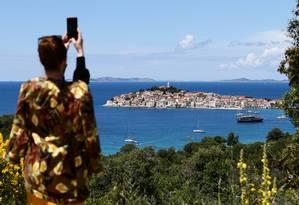 Mulher fotografa a cidade de Primosten, na Croácia Foto: Antonio Bronic / Reuters