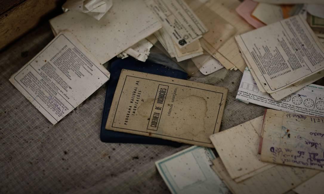Documentos, como uma carteira de vacinação, foram deixados para trás durante a fuga de uma casa agora abandonada no distrito de Socorro Foto: Pablo Jacob / Agência O Globo
