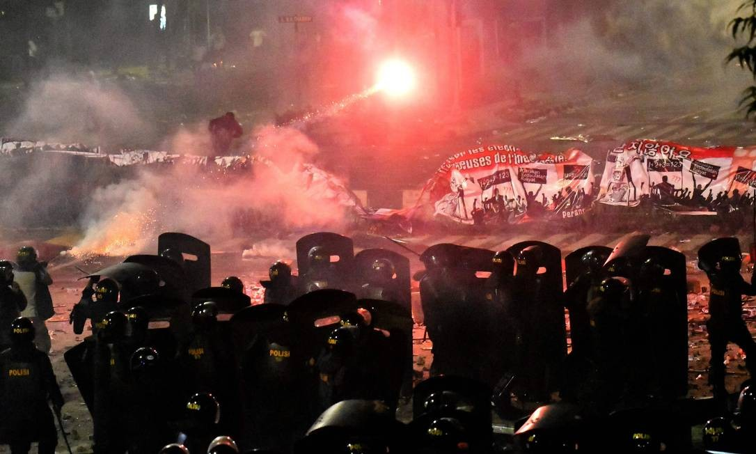 Forças policiais lançam gás lacrimogêneo contra manifestantes que protestam contra a reeleição do presidente indonésio em Jacarta. Pelo menos seis pessoas morreram quando a capital da Indonésia explodiu em violência após a polícia entrar em conflito com manifestantes contrários à reeleição do presidente Joko Widodo. Foto: GOH CHAI HIN / AFP