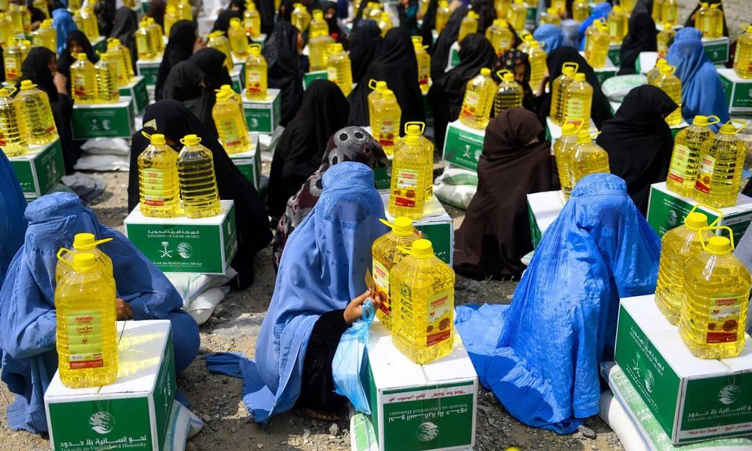 Mulheres de etnia afegã se reúnem enquanto recebem artigos de ajuda de uma instituição de caridade durante o mês sagrado de ramadã na província de Herat. Este é o mês mais sagrado do calendário islâmico, durante o qual os devotos jejuam desde o amanhecer até o anoitecer. Foto: HOSHANG HASHIMI / AFP