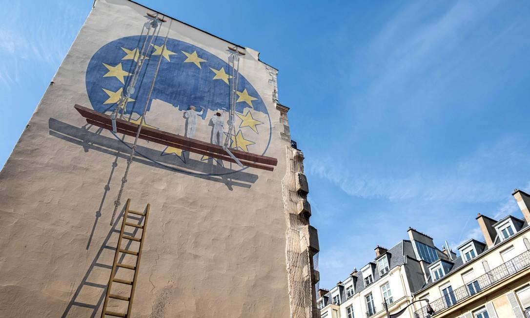 Dois trabalhadores pintam a bandeira da União Europeia ao lado de um prédio na capital francesa, Paris. A Europa iniciou a votação para o Parlamento Europeu em todo o continente. As forças populistas crescentes esperam obter ganhos significativos, ameaçando uma integração mais estreita da UE. Foto: JOEL SAGET / AFP