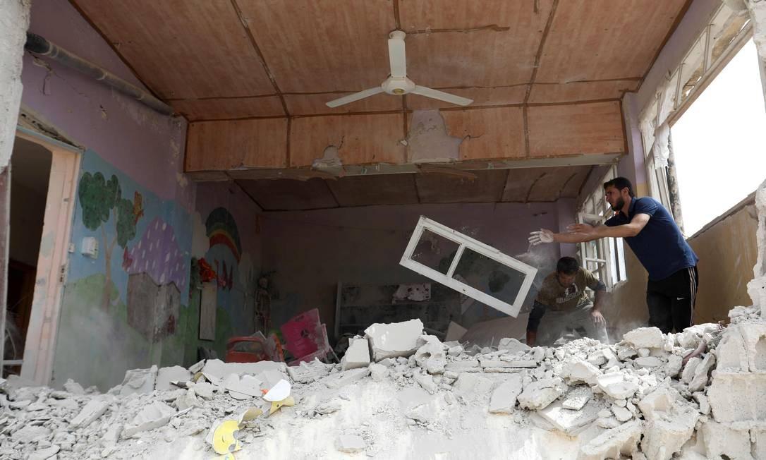 Um homem limpa escombros de um prédio que foi danificado durante um ataque aéreo das forças do governo sírio na cidade de Kafr Aweid. Aviões do governo sírio bombardearam várias cidades no noroeste e mataram oito civis. Foto: OMAR HAJ KADOUR / AFP