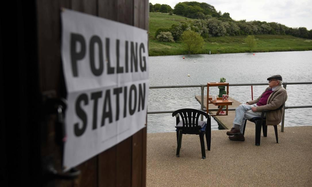 Um homem senta-se em uma estação de votação montada no Rawdon Model Boat Club, perto de Leeds, quando a votação para as eleições do Parlamento Europeu começam em todo o país. A votação começou na Grã-Bretanha na quinta-feira — uma disputa que o país não esperava manter quase três anos após o referendo do Brexit. Foto: OLI SCARFF / AFP