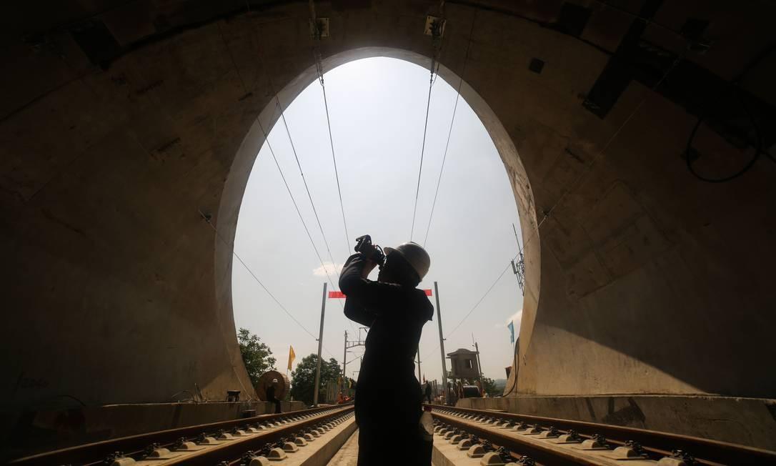 Trabalhador inspeciona linhas aéreas em uma entrada de túnel em uma nova linha da rede ferroviária de alta velocidade da China em Bijie, na província de Guizhou. A nova linha, entre Chengdu e Guiyang, deverá entrar em serviço em dezembro de 2019. Foto: STR / AFP