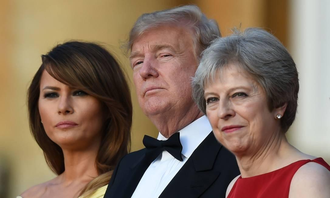 A primeira-dama dos EUA, Melania Trump, o presidente dos Estados Unidos, Donald Trump, e a primeira-ministra britânica, Theresa May durante um cerimonial de boas-vindas com líderes empresariais no Palácio de Blenheim, oeste de Londres, em julho de 2018 Foto: GEOFF PUGH / AFP
