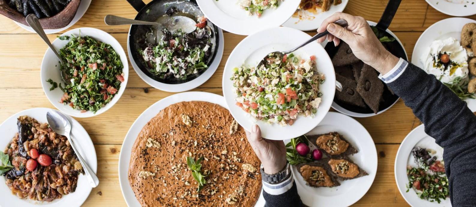 Uma variedade de comidas quentes e frias servidas no Beit El Qamar, no Líbano. A cozinha libanesa tem uma mistura de grãos, frutas, vegetais, castanhas e sementes. Compartilhar uma refeição, hábito do país, pode ser uma maneira de evitar o desperdício e o consumo excessivo Foto: IEVA SAUDARGAITE / NYT