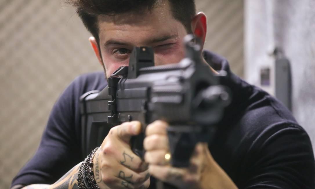 Na foto, Axl Satier, 37 anos, posa com uma arma de grosso calibre Foto: Marcelo Regua / Agência O Globo