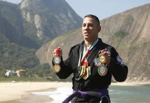 Em casa. Na Praia de Itacoatiara, Moisés Santoro mostra as principais medalhas que já conquistou Foto: Fábio Guimarães / Fábio Guimarães