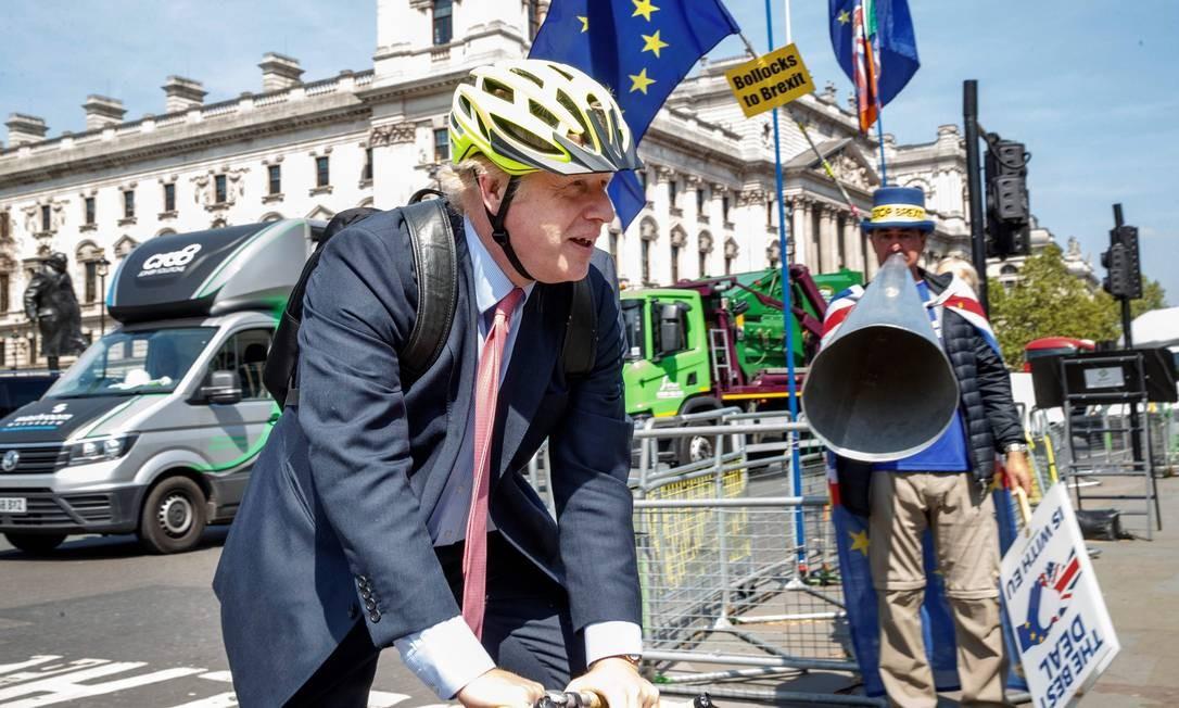O ex-chanceler Boris Johnson chega ao Parlamento de bicicleta, em Londres, diante de um manifestante favorável à permanência do Reino Unido na UE: para críticos, um 'bufão', mas é um dos favoritos a suceder May Foto: Tolga AKMEN/AFP/15-05-2019