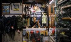 O vendedor Caio exibe armas de fogo disponíveis em loja de Brasília Foto: Daniel Marenco / Agência O Globo