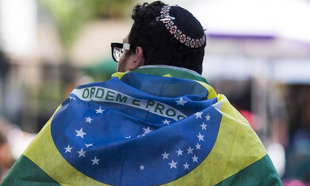 A bandeira do país foi um dos itens mais recorrentes nas manifestações deste domingo. Na foto, um homem leva a bandeira nas costas em São Paulo Foto: Edilson Dantas / Agência O Globo