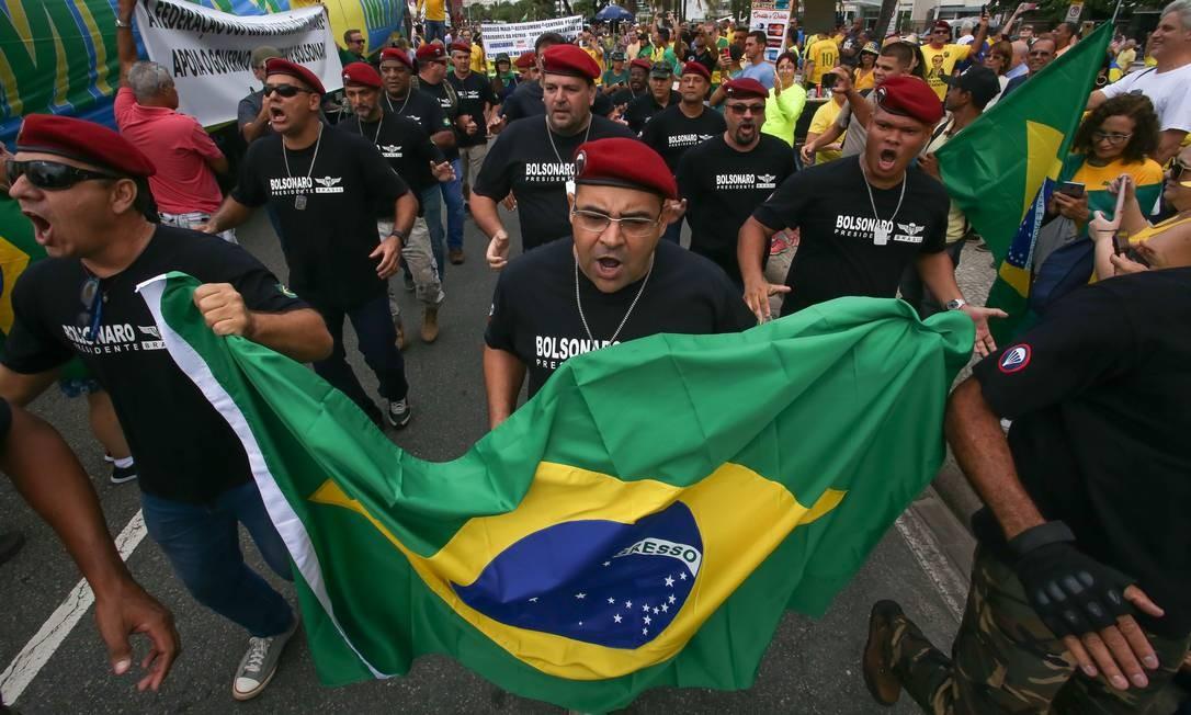 Homens de boinas vermelhas carregam a bandeira do Brasil, em Copacabana Foto: Marcelo Regua / Agência O Globo