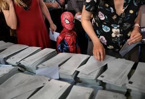 Menino vestido de Homem-Aranha acompanha os pais em votação em seção eleitoral de Madri Foto: SUSANA VERA/REUTERS