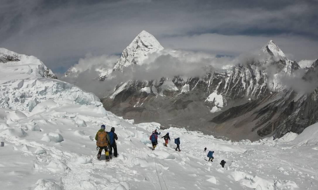 Alpinistas caminham perto do acampamento do Monte Everest, enquanto se preparam para subir na face sul do Nepal Foto: PHUNJO LAMA / AFP