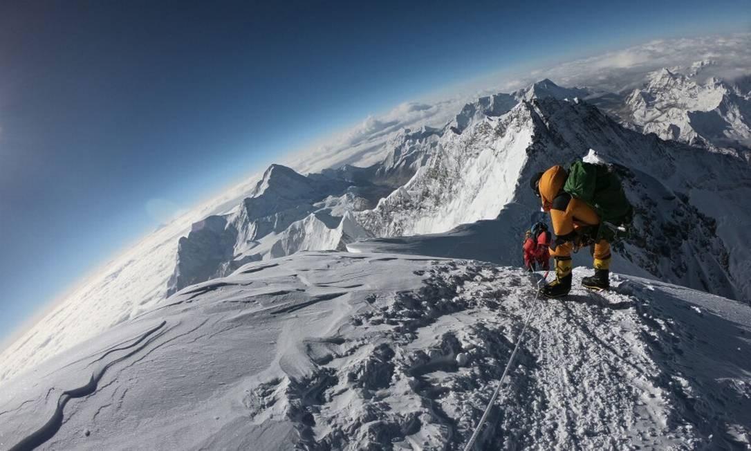 Alpinistas fazem o seu caminho até o topo do Monte Everest, enquanto sobem na face sul do Nepal Foto: PHUNJO LAMA / AFP