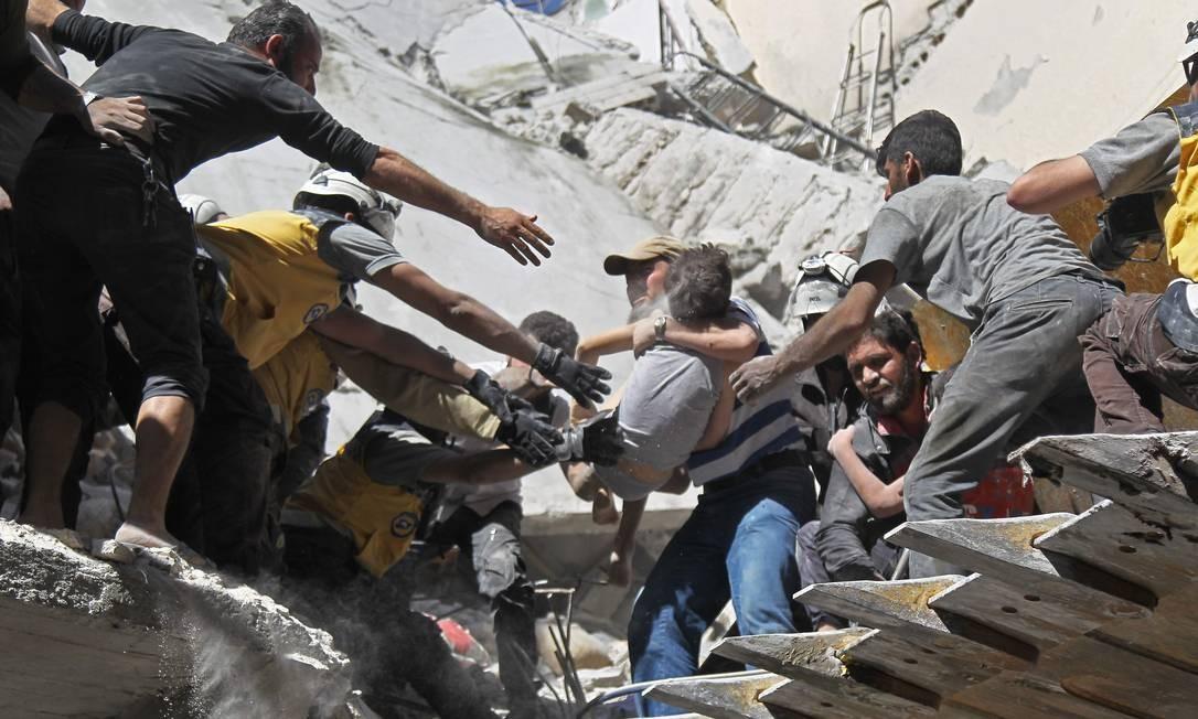 Voluntários do White Helmet resgatam uma criança dos escombros de um edifício destruído durante um ataque aéreo das forças do regime sírio e seus aliados na cidade de Ariha, na periferia sul da província síria de Idlib Foto: AMER ALHAMWE / AFP