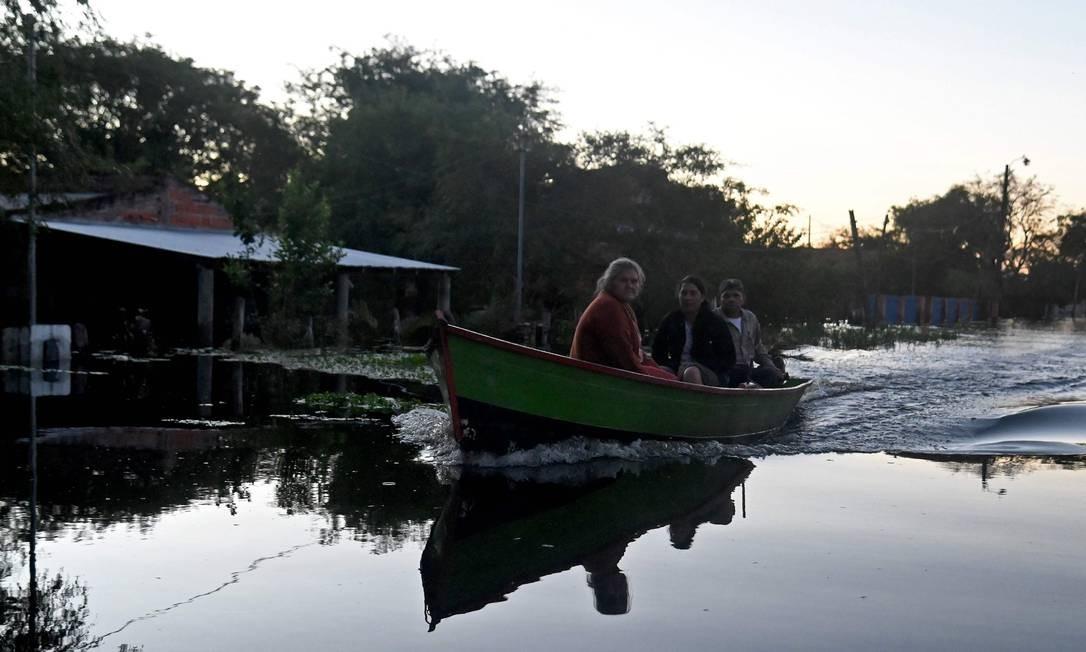 Pessoas usam um barco para se deslocar na cidade inundada de Puerto Falcon, perto de Assunção, depois que fortes chuvas nas últimas semanas causaram o transbordamento do Rio Paraguai Foto: NORBERTO DUARTE / AFP