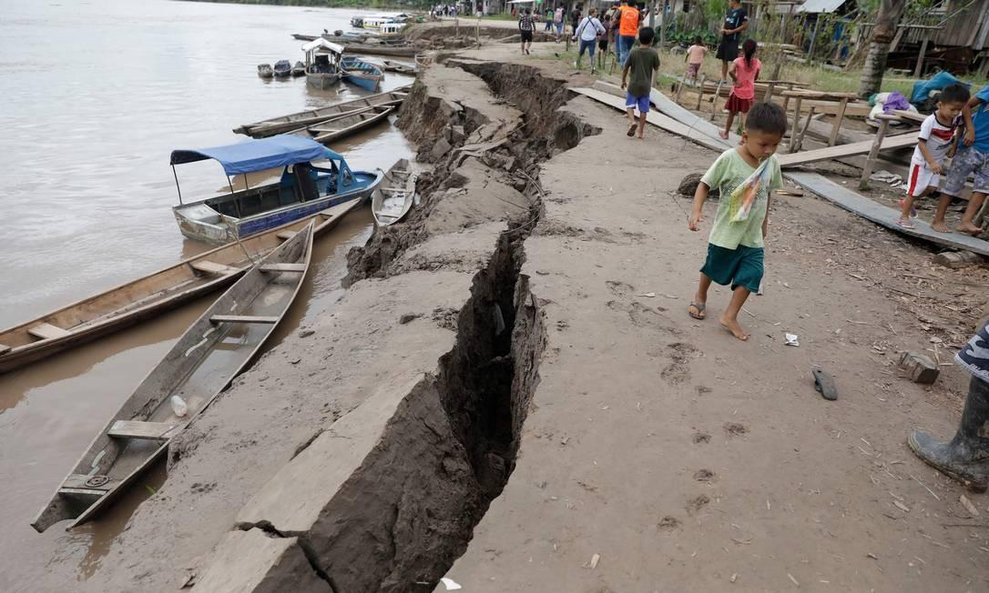 Uma criança anda perto de uma rachadura no chão causada por um terremoto em Puerto Santa Gema, nos arredores de Yurimaguas, na região amazônica, no Peru. Um poderoso terremoto de 8,0 atingiu o norte do Peru no início do domingo, derrubando casas, bloqueando estradas e derrubando o fornecimento de energia para algumas localidades. Uma pessoa foi morta e outras 18 ficaram feridas Foto: GUADALUPE PARDO / AFP