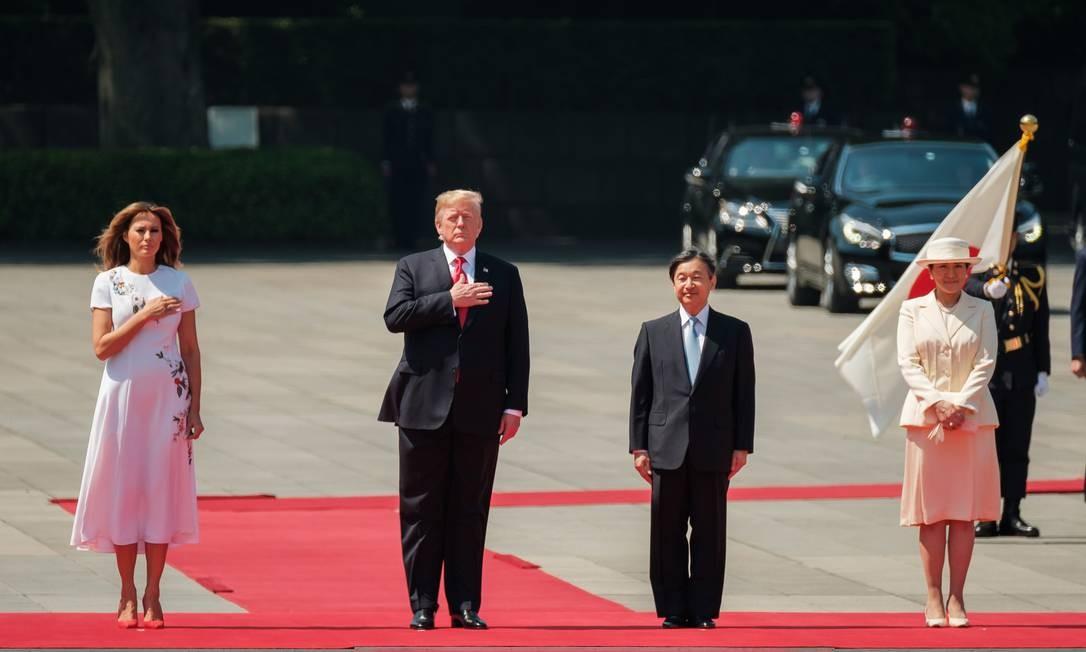 A primeira-dama dos Estados Unidos, Melania Trump, o presidente dos EUA, Donald Trump, o imperador japonês, Naruhito, e a imperatriz, Masako, ouvem os hinos nacionais durante uma cerimônia de boas-vindas no Palácio Imperial em Tóquio Foto: NICOLAS DATICHE / AFP
