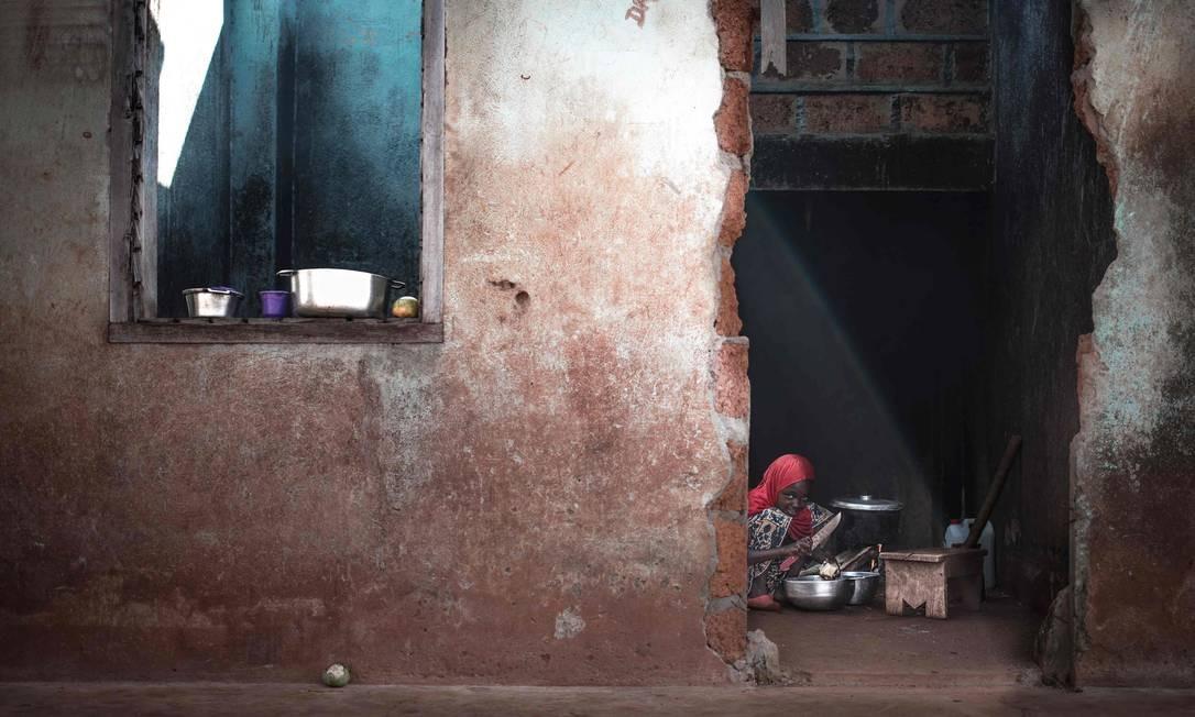 Uma criança cozinhando em sua casa arruinada no distrito Tokoyo de Bangassou Foto: FLORENT VERGNES / AFP
