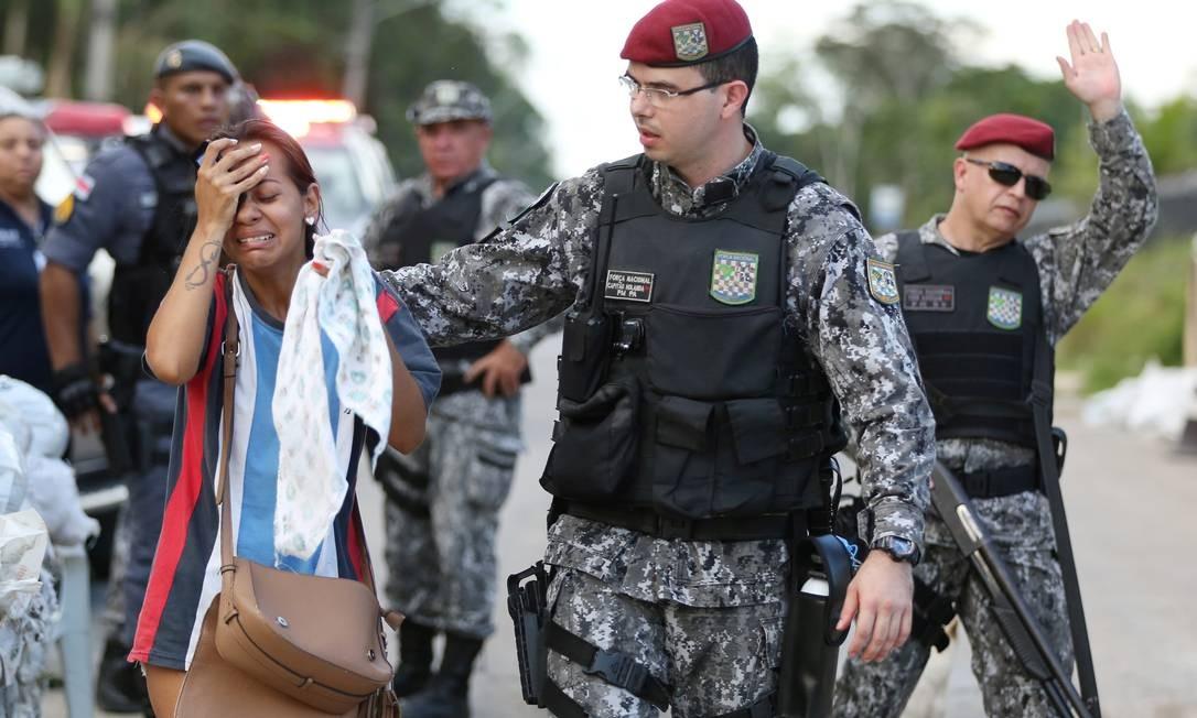 Agente da Força Nacional de Segurança tenta acalmar mulher durante manifestação de parentes diante de presídio em Manaus Foto: BRUNO KELLY / REUTERS