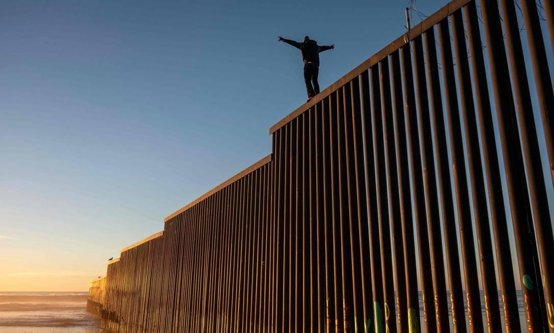 Migrantes hondurenho escalou muro entre EUA e México Foto: GUILLERMO ARIAS / AFP