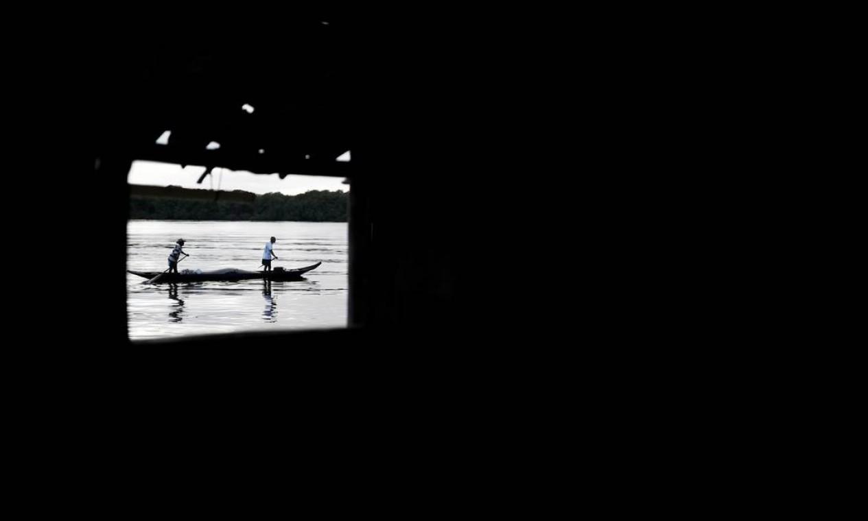 Pescadores em seus barcos são vistos através de uma janela do pescador José da Cruz, no rio Caratingui. Mudanças climáticas estão ameaçando as dezenas de famílias na vila de Cruz que dependem do ecossistema costeiro Foto: NACHO DOCE / REUTERS