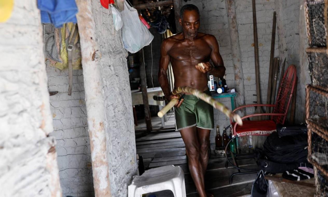 O pescador José da Cruz segura uma cana-de-açúcar dentro de sua casa Foto: NACHO DOCE / REUTERS