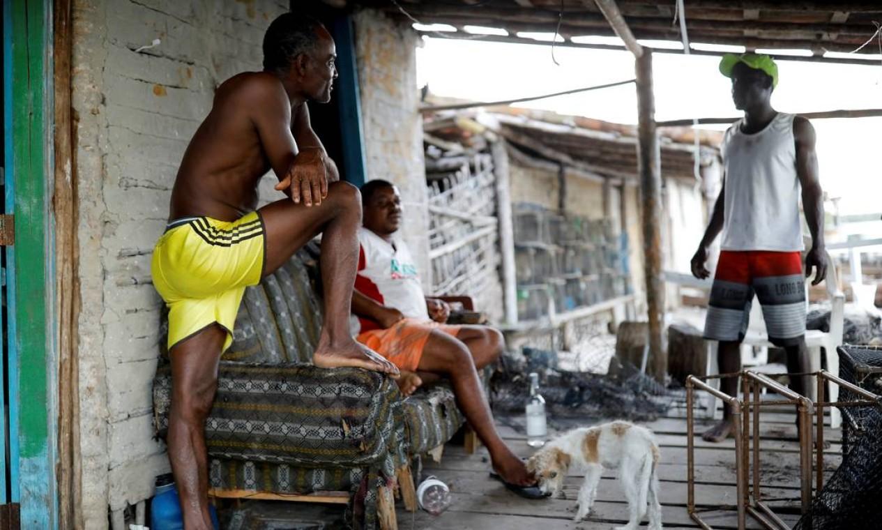 O pescador José da Cruz conversa com vizinhos de fora de sua casa Foto: NACHO DOCE / REUTERS