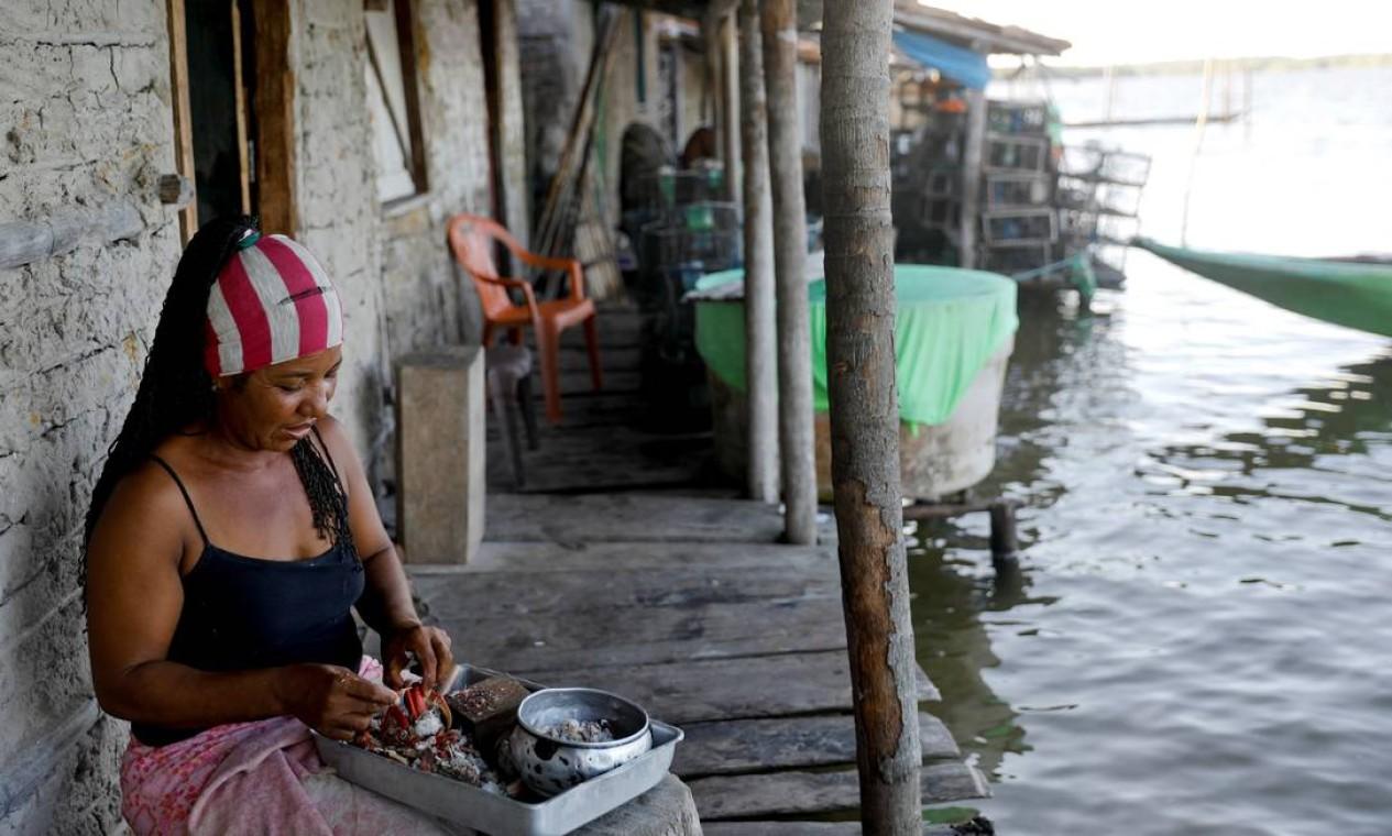 A esposa de Curz, Vandeka, descasca caranguejos para preparar uma moqueca Foto: NACHO DOCE / REUTERS