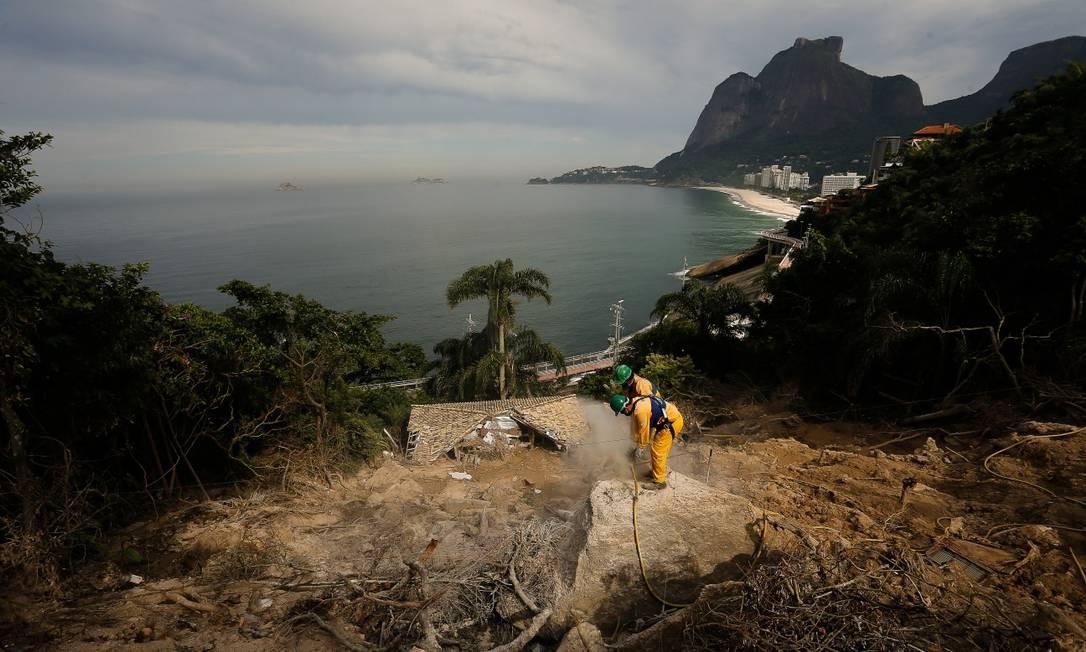 Equipe da prefeitura trabalha, na manhã desta quarta-feira (29), na contenção e retirada de pedras da encosta da Avenida Niemeyer. A via foi interditada para o trânsito na tarde de terça (28), por determinação da Justiça Foto: Pablo Jacob / Agência O Globo
