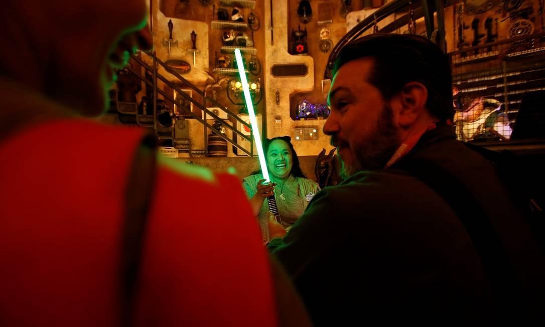 """Vendedora mostra um sabre de luz a clientes na Savi's Workshop - Handbuilt Lightsabers, loja na área temática de """"Star Wars"""" na Disneyland, em Anaheim Foto: MARIO ANZUONI / REUTERS"""