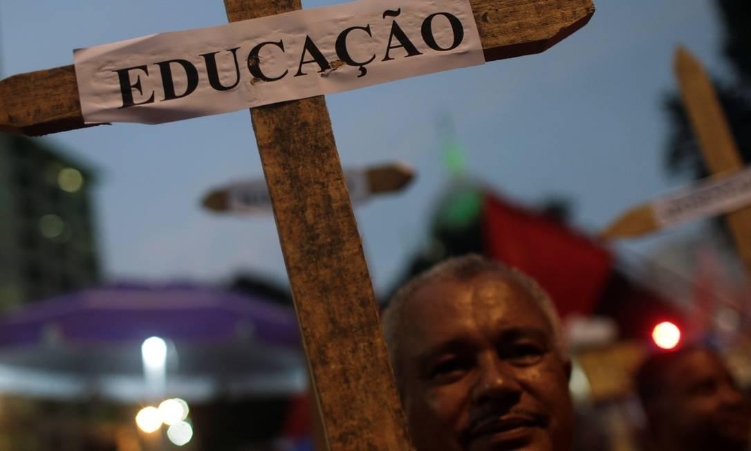 """Um homem segura uma cruz com a placa """"Educação"""" durante um protesto de estudantes contra cortes nos gastos federais no setor planejados pelo governo Bolsonaro Foto: RICARDO MORAES / REUTERS"""