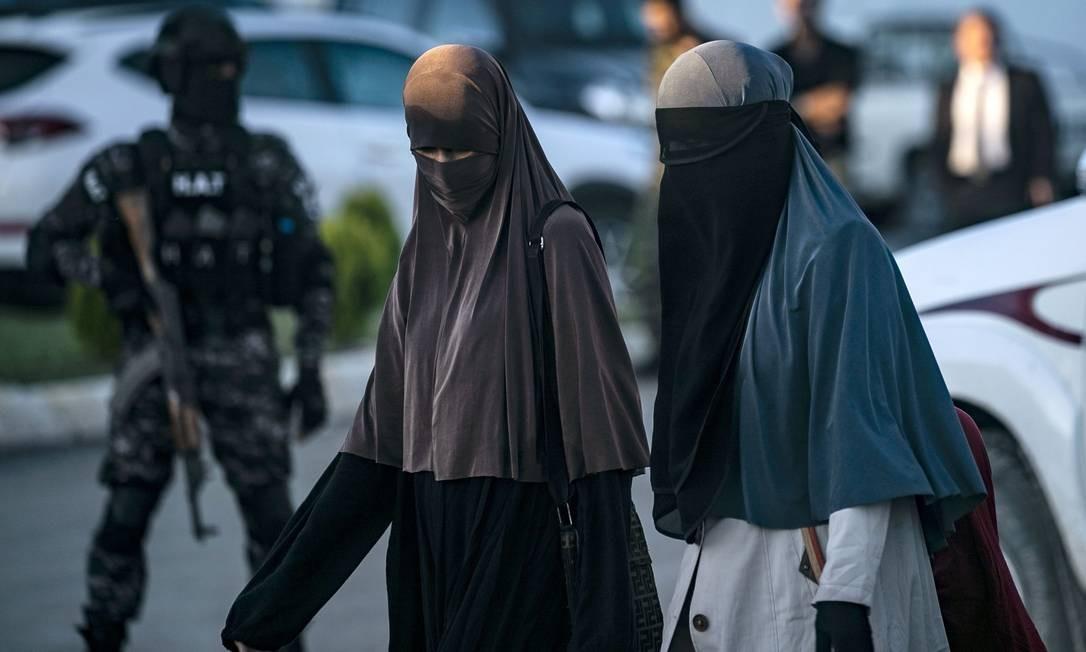 Mulheres totalmente veladas caminham na cidade de Qamishli, no norte da Síria, enquanto mulheres e crianças uzbeques ligadas ao grupo do Estado Islâmico são entregues a diplomatas do país da Ásia Central para repatriação Foto: DELIL SOULEIMAN / AFP
